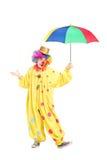 Ganzaufnahme eines netten Clowns, der einen Regenschirm hält lizenzfreies stockbild