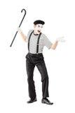 Ganzaufnahme eines Pantomimekünstlers, der einen Stock und ein gesturi hält Stockfotos