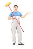 Ganzaufnahme eines Reinigers in einer Uniform mit einem Besen Lizenzfreie Stockfotos