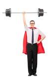 Ganzaufnahme eines Superhelden, der ein Schwergewicht hält Stockbild