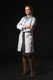 Ganzaufnahme ernster Doktorfrau auf schwarzem Hintergrund Lizenzfreie Stockbilder
