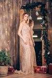Ganzaufnahme sexy eleganten Blondine in einem langen goldenen Kleid nahe dem Spiegel verziert mit Weihnachtsniederlassungen und lizenzfreie stockfotos