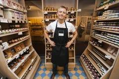 Ganzaufnahme von stehenden Händen des mittleren erwachsenen Verkäufers auf Hüften im Gemischtwarenladen Lizenzfreie Stockfotografie
