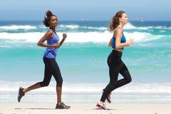 Ganzaufnahme von zwei geeigneten jungen Frauen, die auf Strand laufen Stockbild