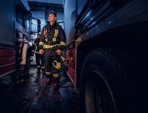 Ganzaufnahme von zwei tapferen Feuerwehrmännern in der schützenden Uniform gehend zwischen zwei Feuerspritzen in der Garage von stockfotografie