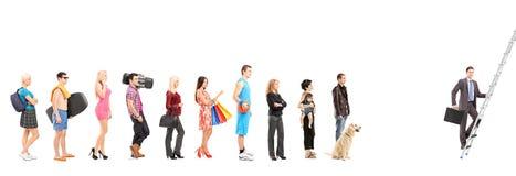 Ganzaufnahmen von den Leuten, die in eine Linie und in ein Geschäft warten Lizenzfreie Stockfotos