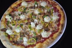 Ganze feinschmeckerische Pizza mit geschnittener italienischer Wurst, Ricotta-Käse und Bananen-Pfeffern Lizenzfreie Stockfotos