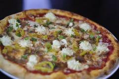 Ganze feinschmeckerische Pizza mit geschnittener italienischer Wurst, Ricotta-Käse und Bananen-Pfeffern Stockfotografie