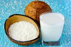Ganze frische Kokosnuss, Kokosnusschips und Kokosmilch in einem Glas O stockfotos
