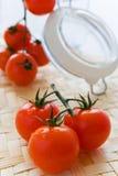 Ganze frische rote Tomaten und Glasgefäß Lizenzfreie Stockfotos