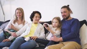 Ganze gl?ckliche Familie sitzt auf Sofa und entspannt sich, indem sie w?hlt und fernsieht stock video footage