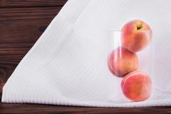 Ganze schmackhafte rote Pfirsiche auf einer weißen Tischdecke Drei gesund und organische Pfirsiche in einem Glas auf einem hölzer Lizenzfreie Stockfotografie