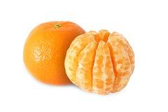 Ganze Tangerinefrüchte und abgezogene Segmente lokalisiert stockfotografie