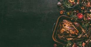 Ganzer gebratener Truthahn, angefüllt mit Trockenfrüchten in der Bratwanne für Weihnachtsessen, gedient auf dunklem Tabellenhinte stockbild