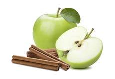 Ganzer grüner Apfel und Hälfte plus die Zimtstange lokalisiert stockfotografie