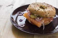 Ganzer Korn-Bagel mit Lachs-, Frischkäse, Zwiebeln und reiner Essiggurke Lizenzfreie Stockbilder
