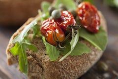 Ganzer Kornzwieback mit sonnengetrockneten Tomaten und Rakete stockfotografie