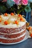 Ganzer selbst gemachter Karottenkuchen auf der Platte mit frischen Blumen auf dem Hintergrund Lizenzfreies Stockfoto