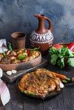 Ganzes Brathähnchen in einem Eisenstein mit Ofenkartoffel und Wein Georgisches tapaka Huhn Dunkler Hintergrund lizenzfreie stockfotografie
