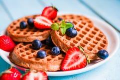 Ganzes Korn waffles mit Beeren auf blauem hölzernem Hintergrund Stockbilder