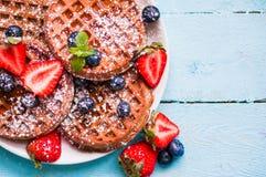 Ganzes Korn waffles mit Beeren auf blauem hölzernem Hintergrund Stockfoto