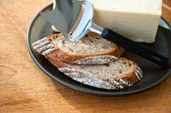 Ganzes Kornbrot, -käse und -messer auf einer Platte Stockfotos