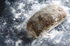 Ganzes Laib des hefefreien Brotes auf Mehl, dunkle Oberfläche Konzept von unterstützten Waren lizenzfreie stockfotografie