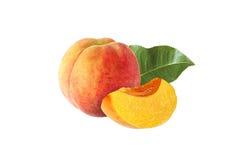Ganzes und halber Pfirsich mit dem Blatt lokalisiert stockfotografie