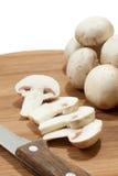 Ganzes und Pilze in Scheiben mit Messer auf hölzernem Brett Stockfotografie
