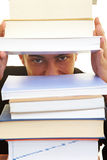Gap in books. Man looking through a gap in a stack of books Stock Photo