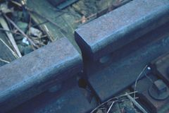 Gap with nut and on the old rusty rail. Rusty train railway detail, oiled sleepers. And stones between rail way stock photography