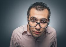 Gape man. Gape young nerd man looking to you through eyeglasess over gray dark background, close up head studio shot Royalty Free Stock Images