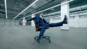 Gappy, funny office manager is riding on a rolling chair across an empty hall. Office manager is riding on a rolling chair across an empty hall. 4K stock video