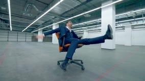 Gappy, grappige bureaumanager berijdt op een rollende stoel over een lege zaal stock video