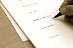Gaps in Communication. Monochrome photograph of a hand writing on a business review form Royalty Free Stock Photo