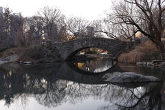 Gapstow Bridge as seen from the Pond. With reflections in the water in New York's Central Park in Winter Stock Images