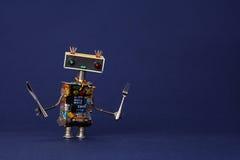 Garçom amigável do robô com forquilha e faca Caráter de cozimento bonito na obscuridade - azul do brinquedo do cozinheiro chefe d fotografia de stock