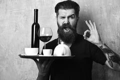 Garçom com vidro e garrafa do vinho pelo chá na bandeja O homem com barba guarda várias bebidas no fundo bege da parede fotografia de stock
