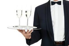 Garçom do homem adulto que serve dois vidros do champanhe isolados Fotografia de Stock