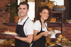 Garçom e empregada de mesa de sorriso que guardam placas com deleite Fotografia de Stock