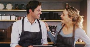Garçom e empregada de mesa de sorriso que usa a tabuleta digital ao falar entre si filme