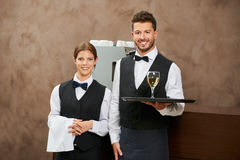 Garçom e empregada de mesa que servem o vinho branco fotos de stock royalty free