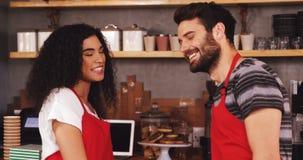 Garçom e empregada de mesa que sorriem no café vídeos de arquivo