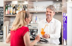 Garçom que dá o cocktail à mulher imagem de stock royalty free