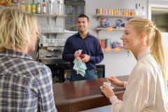 Garçom que espera para tomar a ordem de duas mulheres no café imagem de stock royalty free