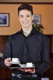 Garçom que traz a xícara de café quente Foto de Stock Royalty Free