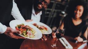 Garçom Serving Salad ao restaurante africano dos pares imagens de stock royalty free