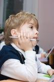 Garçon à l'école dans la salle de classe Photos stock
