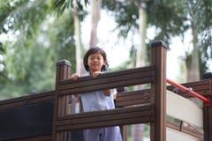 Garçon à l'école uniforme jouant dans le terrain de jeu photo stock
