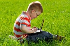 Garçon à l'aide de son ordinateur portatif extérieur dans le stationnement Image stock